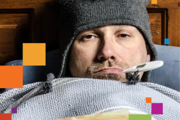 man in bed with knit cap and thermometer