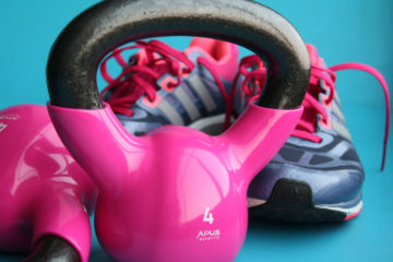 weights and shoes in bright pink on blue background