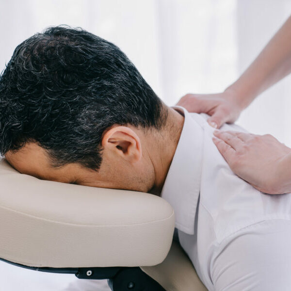 close-up shot of masseuse doing seated back massage for businessman