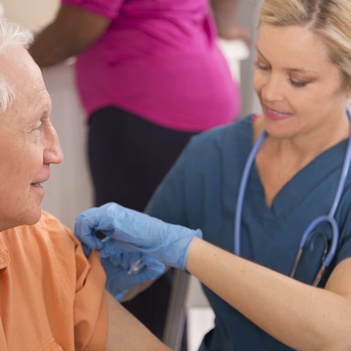 Nurse gives flu vaccine to senior adult patient at pharmacy.
